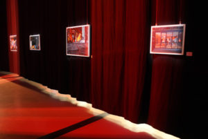 Paintings on a black curtain with a red imminent glow.
