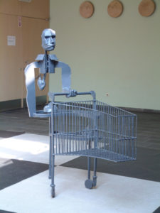A metal sculpture of a half man with a shopping cart on a black and white carpet.