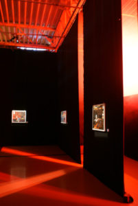 Real exhibition view space with paintings and a red glow that represents a threat.