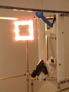 Installation with a self shooting mechanism and a mirror with lights.