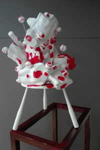 White and red sculpture with male body and baseball bats.