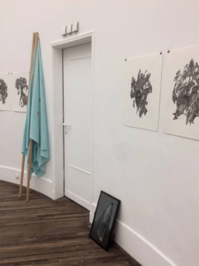 Exhibition view videowork woman in burqa, drawings and flags.