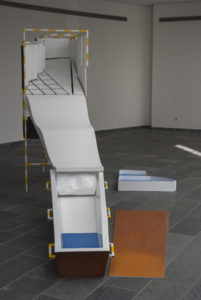 Installation with a coffing and a slide with rusty and blue elements by Niko Hendrickx.