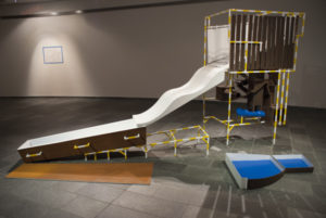 Exhibition view with an installation with a rusted coffin, a slide and blue elements.