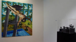 Exhibition view with painting of a diving Jesus with artwork of Raymond Minnen.