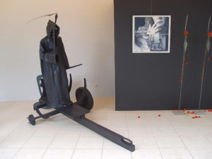 Exhibition view with a black metal sculpture of a grim reaper and an oil painting.