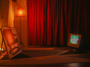 Exhibition view of a living room build up with panels and a old television by Niko Hendrickx.