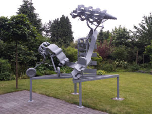 Metal sculpture of an abstract airplane in a garden.