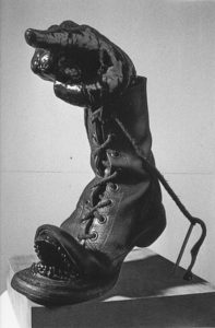 Artwork with a pointing hand in a shoe with theet, the laces are attached to two nails.