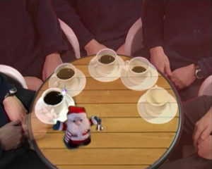 Videostill of a man sitting at a table with coffee and a santa claus doll.