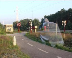Videostill of a ghost crossing a train crosswalk.