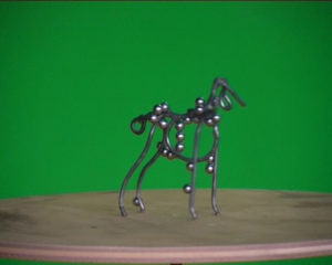 A small wireframe dog with magnetic balls on it.
