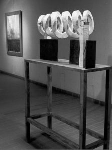 Exhibition view of a wooden spiral on a pedestal.