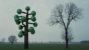 A tree with inflatable volumes next to a natural tree.