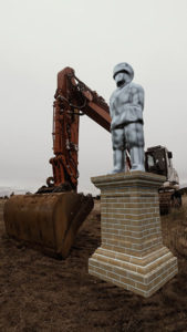 A chrome monument representing power bends over next to an excavator..