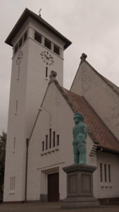 A bronze monument bends over in front of a church.