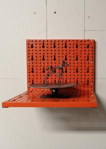 Sculpture dog on a turntable, magnetic balls on the orange metal back plate.