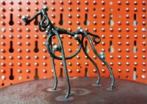 Close up dog sculpture with magnetic balls attached to it.