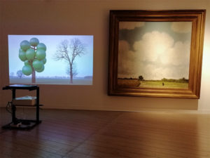 Exhibition view with a projection of an inflatable tree next to a landscape painting from Jacob Smits.