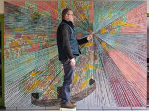 Man in front of a large drawing pointing to the middle of the drawing.